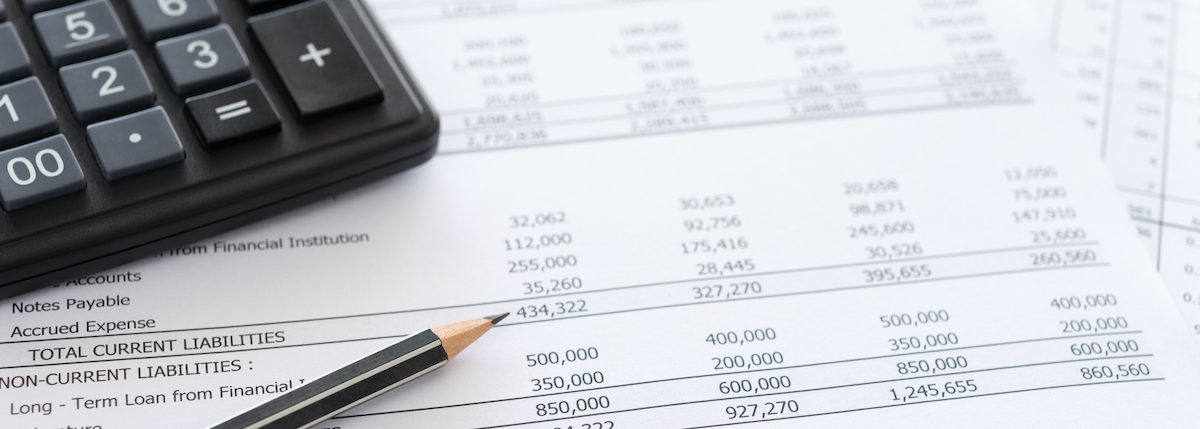photos of financial reports and calculator used for outsourced CFO services